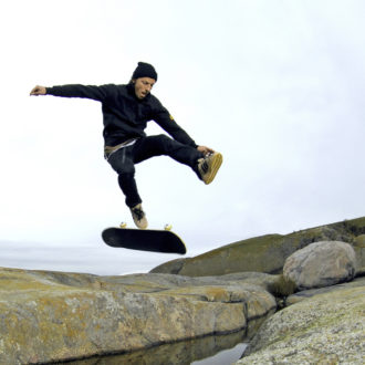 A man does a skateboard trick outside on a large rock surface.