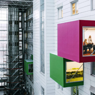 The courtyard of a high-rise building, with rooms designed as colourful cubes sticking out of the wall.