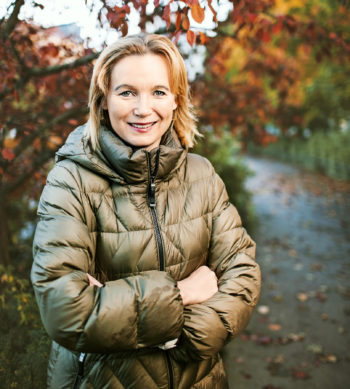 A woman in a jacket smiles in front of autumn-coloured trees.