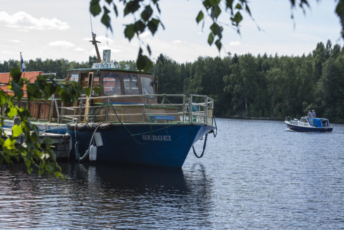 Boat Sergei docked at a pier on a lake.