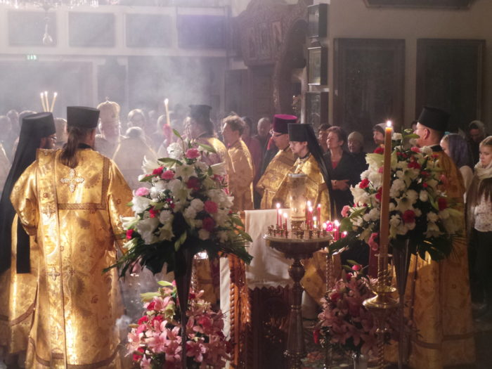 Monks clad in golden robes in the monastery, incense forming smoke over the monks.