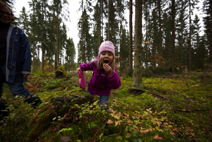 A young girl putting something in her mouth in a forest.
