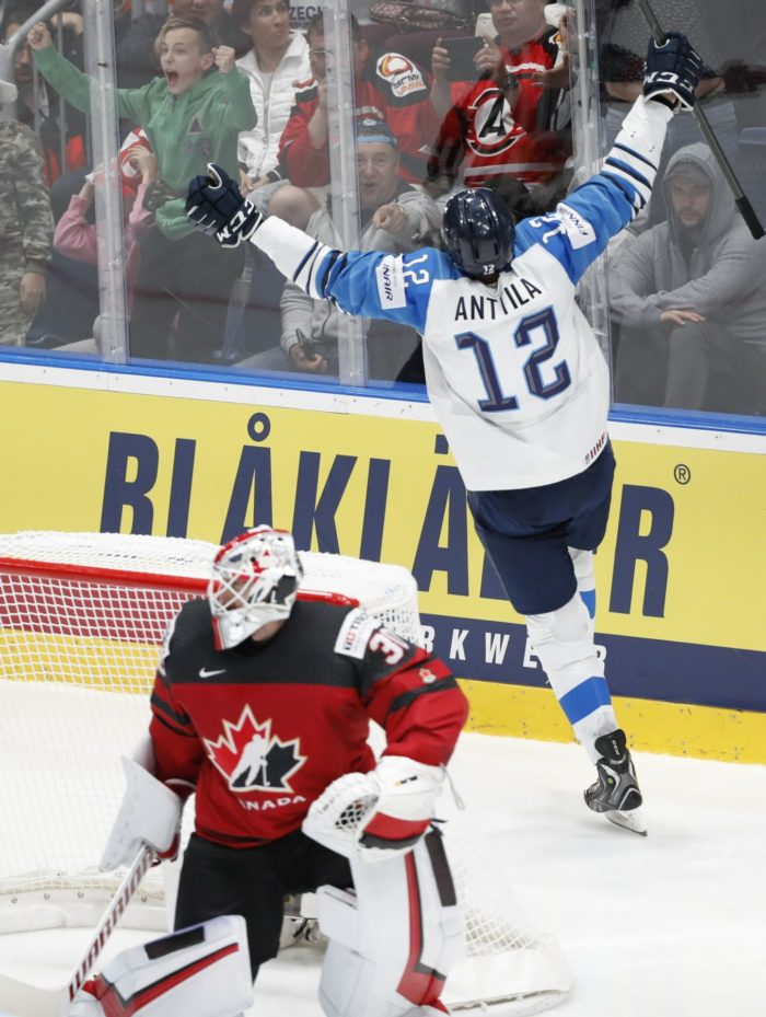 Finnish ice hockey player celebrating a goal while the Canadian goalie kneels by the goal.