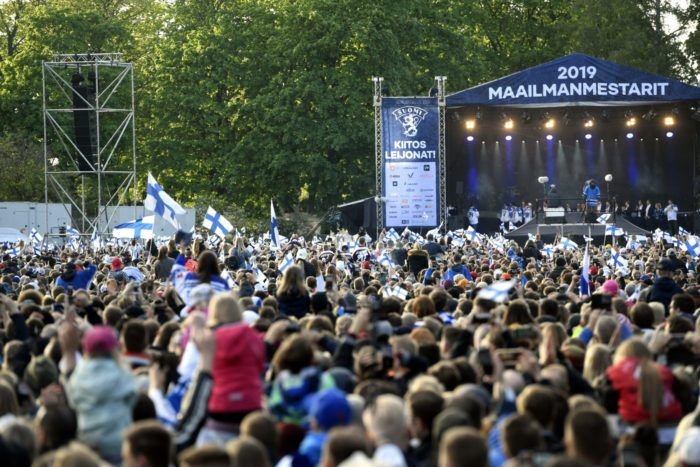 A large crowd gathered by a stage where the Finnish ice hockey team is.