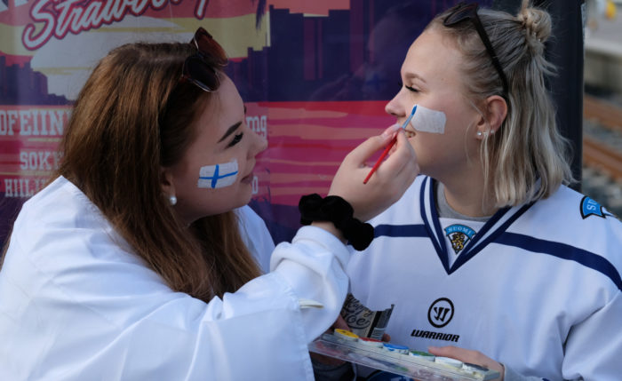 A girl painting the Finnish flag on another girl's cheek.