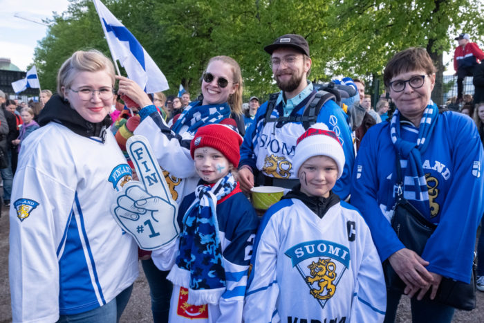 Four adults and two children dressed in Finland fan gear posing for the camera.