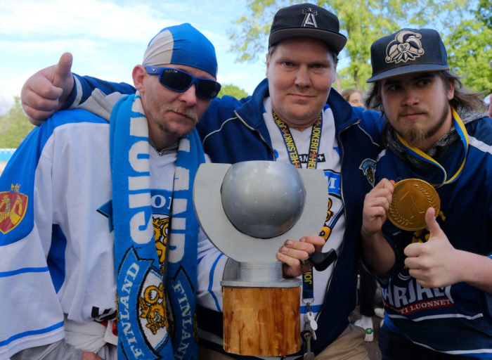 Three men dressed in Finland fan gear posing with a copy of the ice hockey trophy and gold medal.