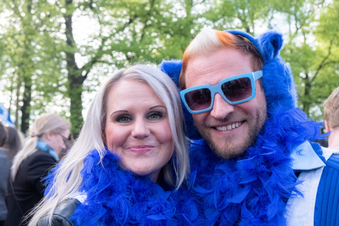 A smiling couple with a blue muff around their necks.