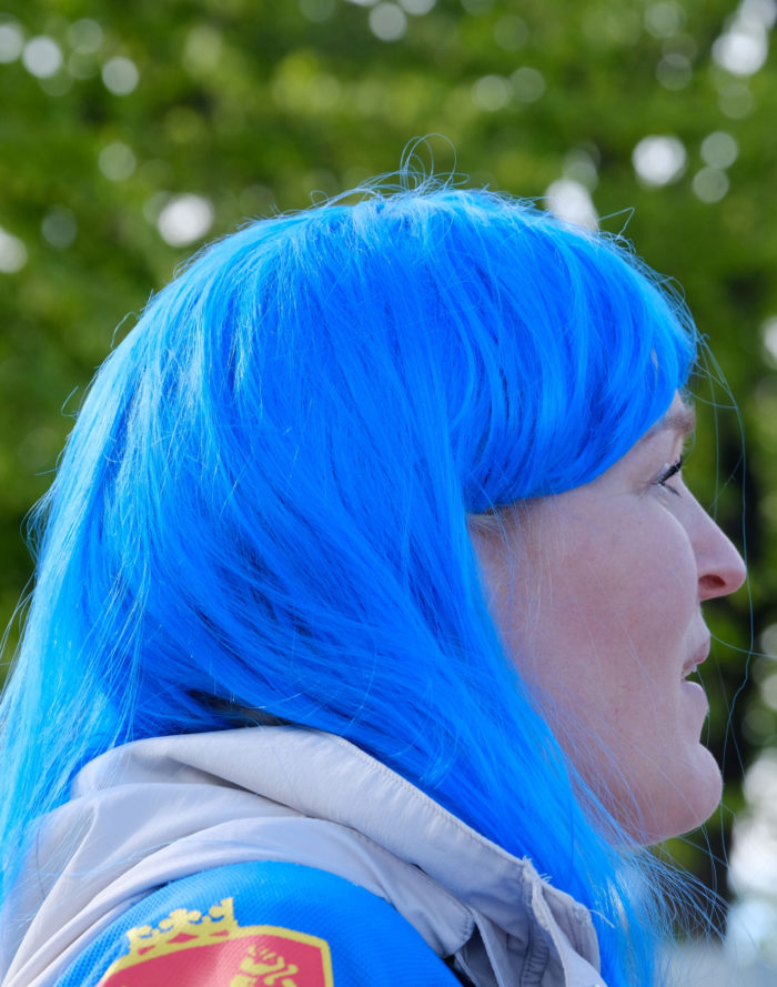 Profile of a woman with bright blue hair.
