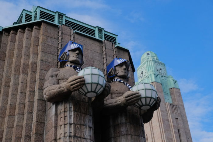 Statues at Helsinki Central Railway Station wearing ice hockey helmets and scarves.