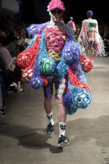 A model on the catwalk wearing colourful crocheted nets with footballs in them.