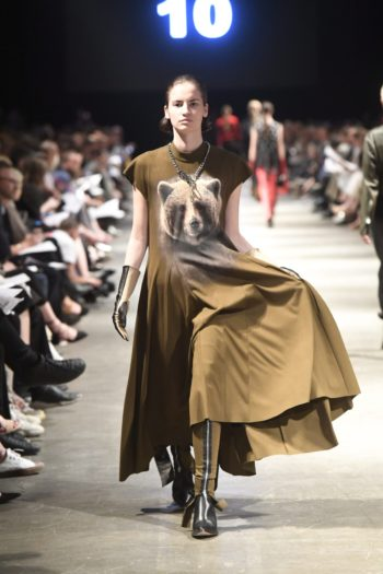 A model on a catwalk wearing a brown dress with an image of a bear.