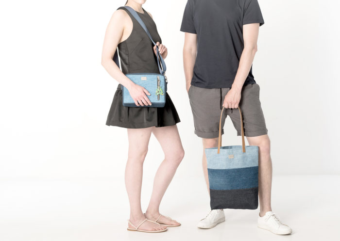 A woman and man showcasing Globe Hope clothes and bags.