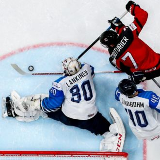 Finland's ice hockey goalie blocking a shot by a Canadian player.