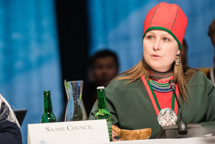 A woman dressed in traditional Sámi clothes sitting by a council table.
