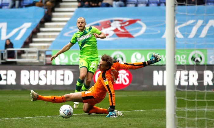 Teemu Pukki shooting the ball towards the goal, a goalkeeper trying to stretch to a save.