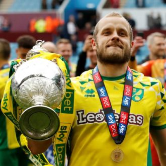 A touched Teemu Pukki dressed in Norwich FC jersey holding a large trophy.