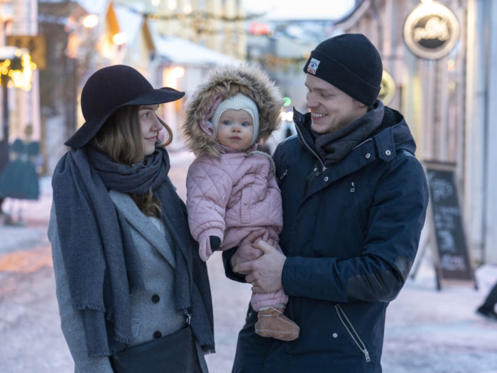 A woman and a man holding a toddler standing on a wintry street.