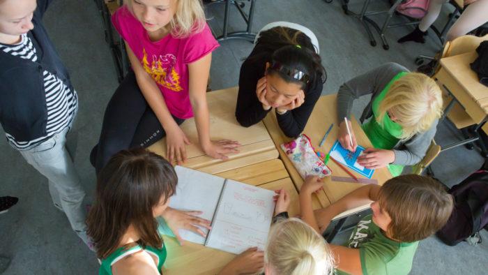 A group of schoolchildren gathered around their desks studying a notebook.