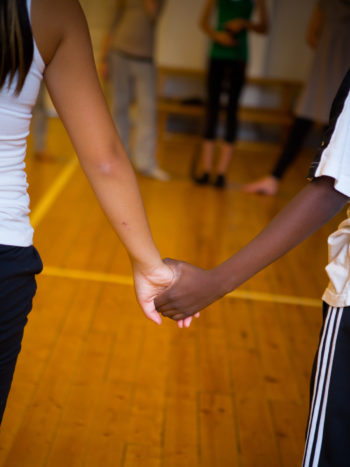 Two schoolchildren holding hands in a gymnasium.