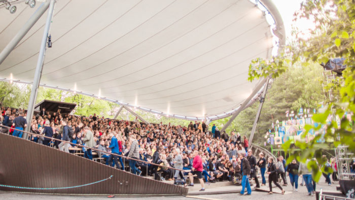 A large crowd sitting on outdoor theatre stands under a big canopy.