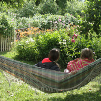 Two children sitting in a hammock in a lush green garden.