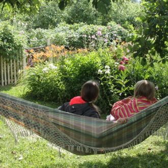Two children sit in a hammock in a lush green garden.