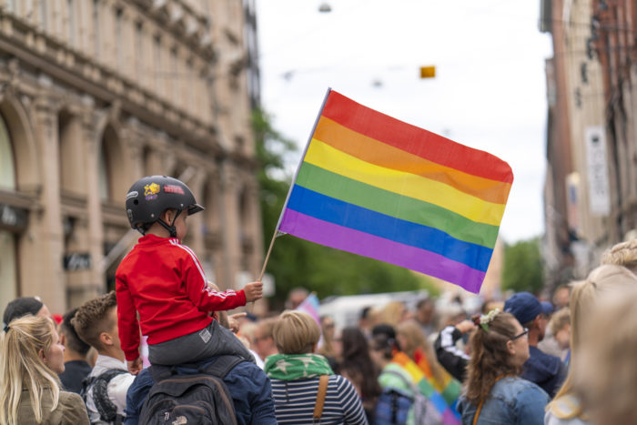 A young boy sitting on the shoulders of an adult and waving a big rainbow flag amidst other parade-goers.