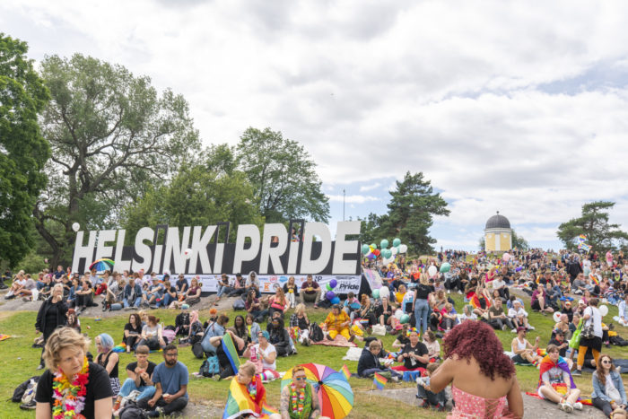 A large crowd of people sitting on the lawn in Kaivopuisto park, a big Helsinki Pride sign in the background.
