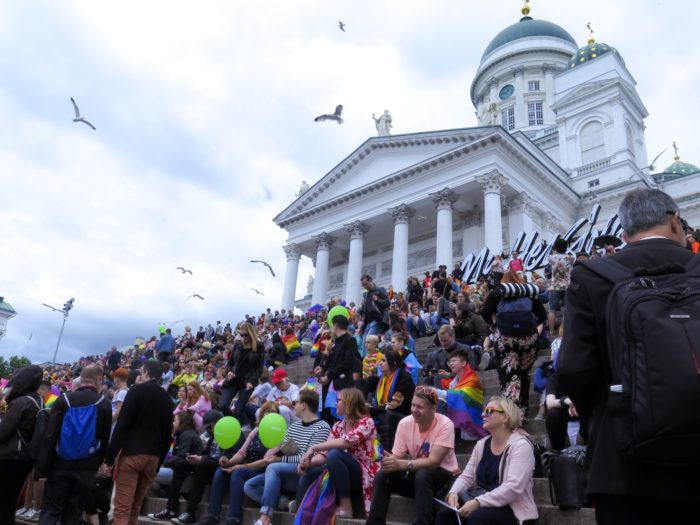 A large crowd of people sitting on the stairs of Helsinki cathedral.