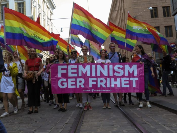 A group of people walking on the street waving rainbow flags and holding a large banner saying 'Feminism gives you freedom' in Swedish.