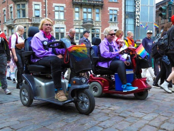 Two elderly people participating in the parade on their senior scooters.