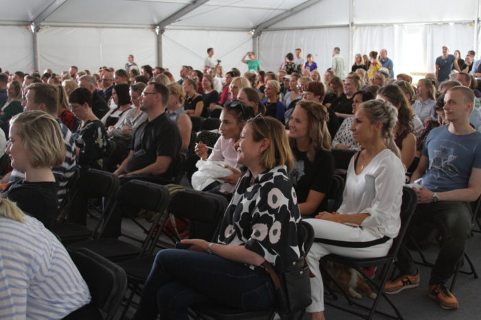A large crowd sitting on chairs inside a white tent.