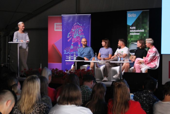 Five people and a host gathered for a panel discussion on a small stage with a small crowd watching.