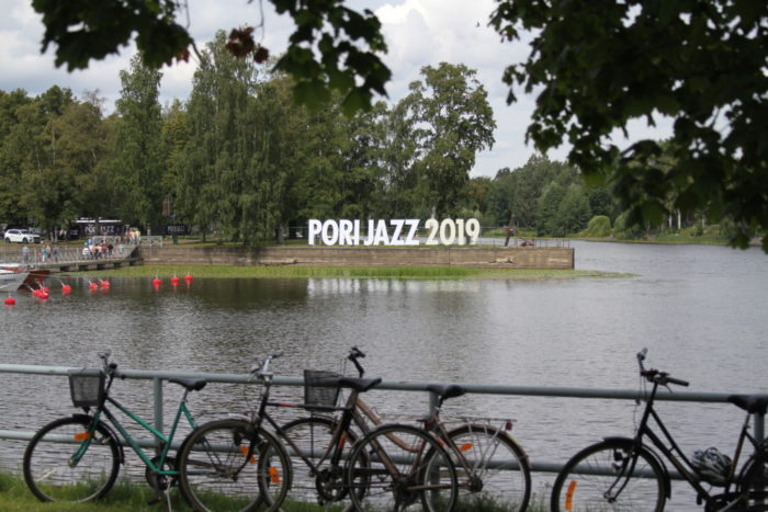 A riverbank with bicycles; Pori Jazz 2019 sign on the opposite bank.