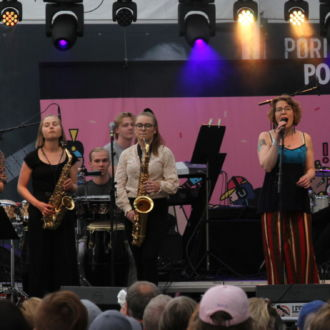 A jazz band performing on a stage with a crowd gathered to see them.