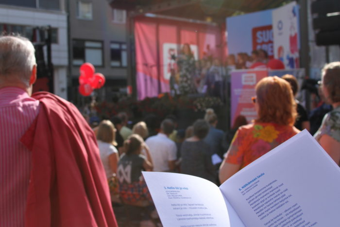 A person holding a leaflet with song lyrics in a crowd gathered by a small stage.