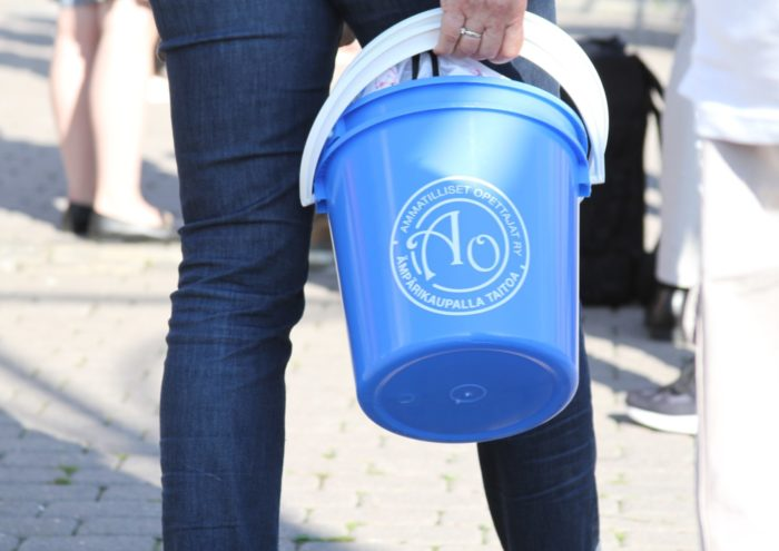 A person carrying a light blue plastic bucket.