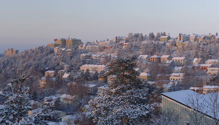 Snow-covered trees and apartment buildings stand on a hillside.