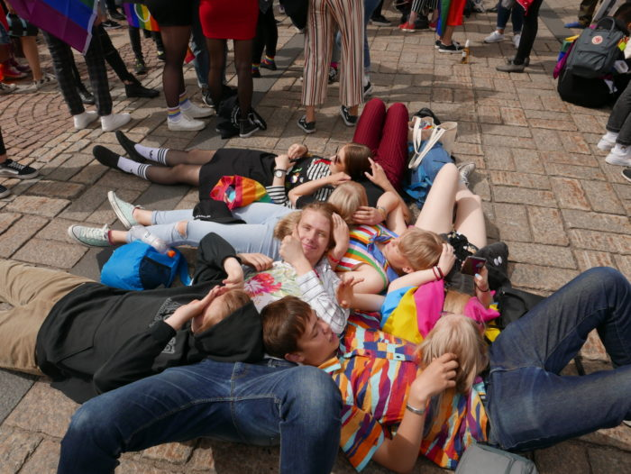 A group of smiling young people lying on the ground.