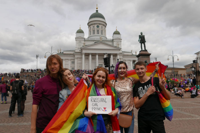 Five people with rainbow flags standing in front of the Helsinki cathedral; the person in the middle is holding a sign saying 'Russian, gay and proud'.