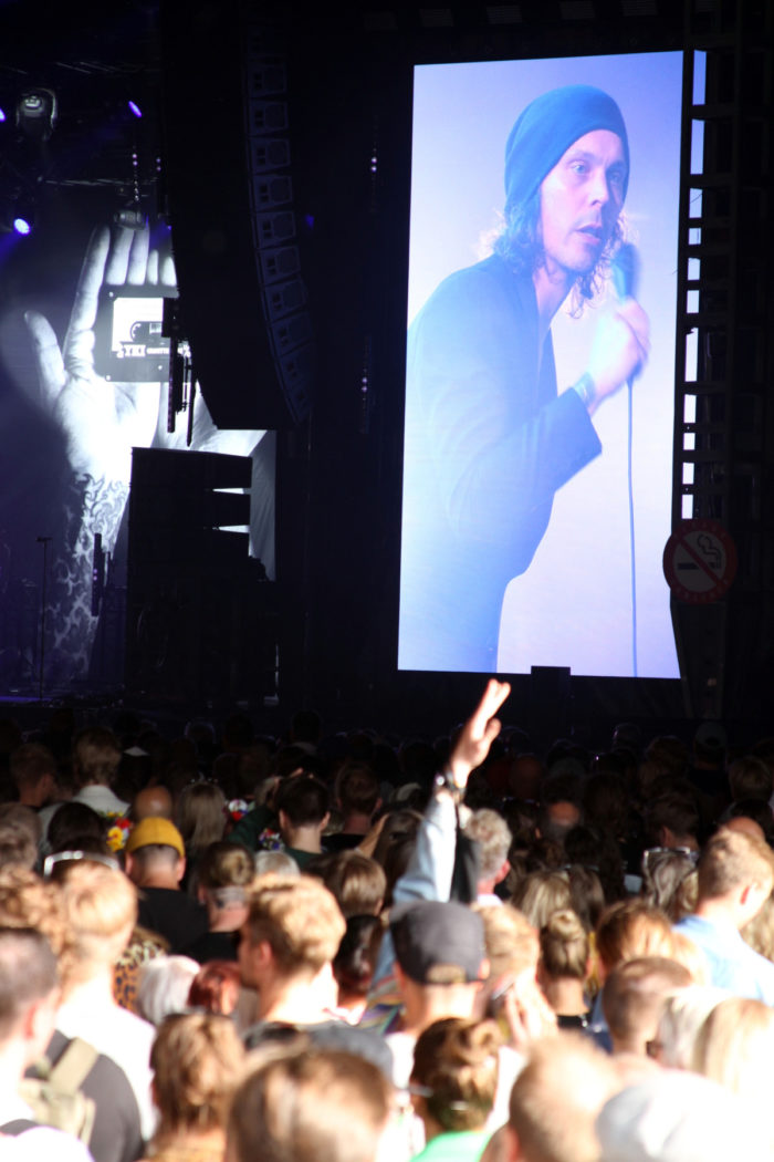 A crowd listens to a Ville Valo concert, with Valo visible on a huge screen by the stage.