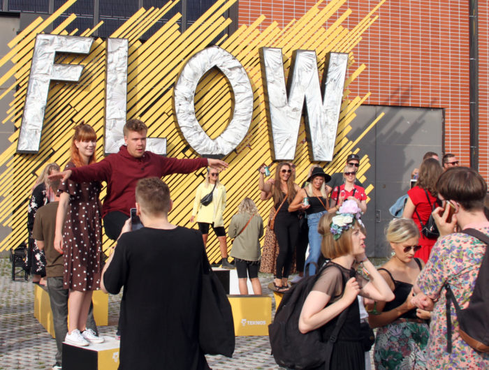 People pose for photos in front of a big sign that says Flow.