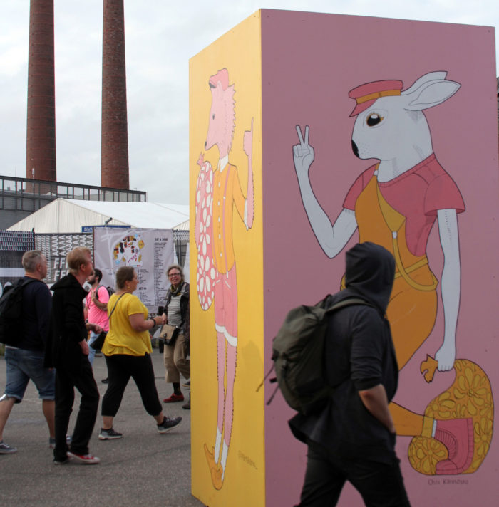 Festival-goers admire artwork, paintings on enormous boxes showing animals wearing clothes.