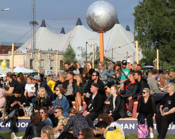 A crowd of festival-goers sits on benches, with an enormous white tent in the background.