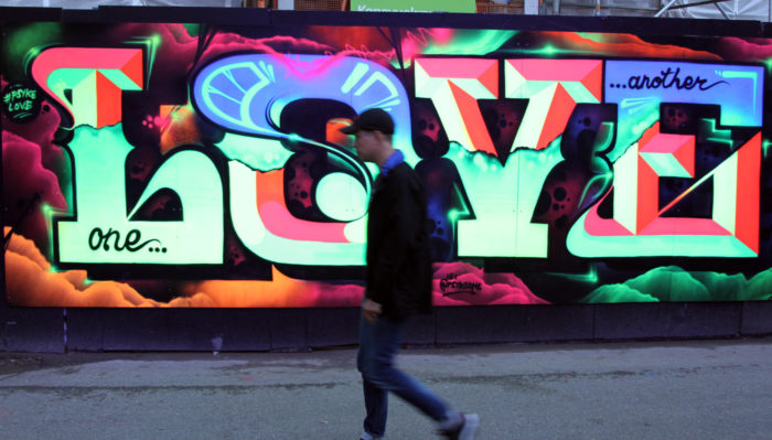 A festival-goer walks past a big and colourful work of graffiti that says Love.