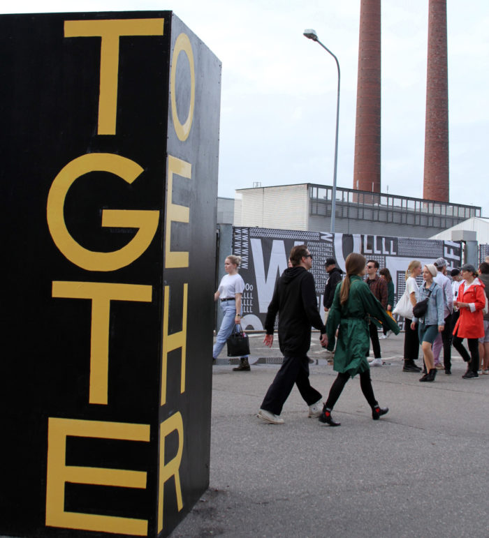 Festival-goers walk past a work of street art that says Together.