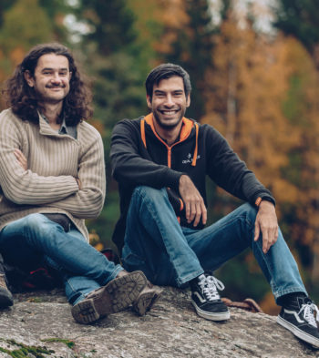 Two men sit on a large rock in a forest.