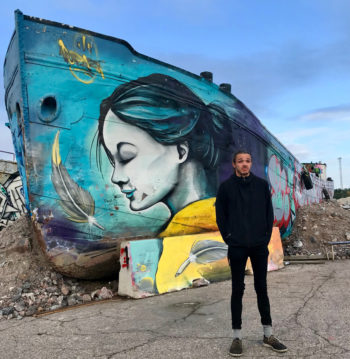 A man standing in front of street art painted on an old ship.