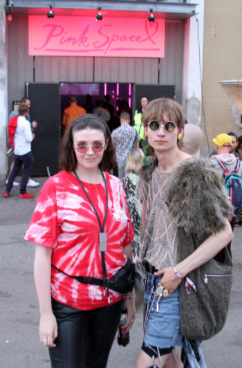 Two festival-goers posing outside of a building with a sign on the wall that says Pink Space.